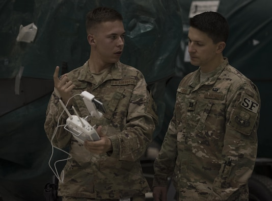 Airman 1st Class Brandon Cooper, 455th Expeditionary Security Forces Squadron, explains the unmanned aircraft systems program to then-Capt. Tyler Hughes, the 455th ESFS commander, during a live-demonstration at Bagram Airfield, Afghanistan, June 30, 2017. The 455th ESFS teamed up with a researcher from the Air Force Research Lab to teach Airmen how to pilot drones and use them to train coalition partners on how to react to them on the battlefield. (U.S. Air Force photo by Staff Sgt. Benjamin Gonsier)