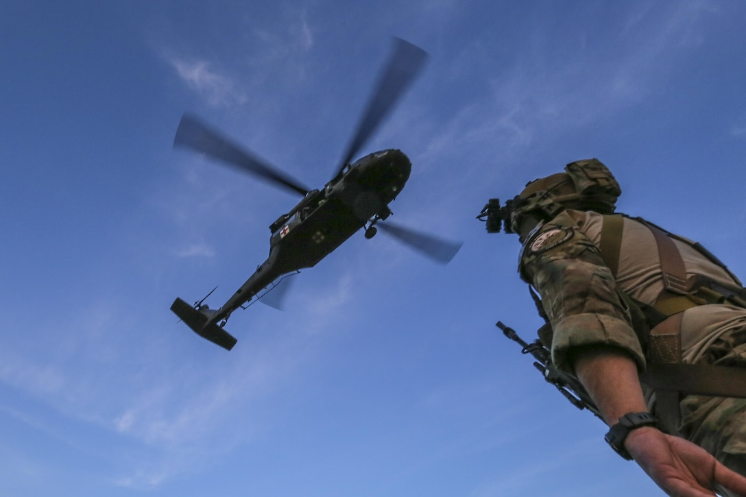Senior Airman Sean Meehan, a tactical air control party Airman from the 227th Air Support Operations Squadron assigned to New Jersey Task Force One, looks up at a hovering Army National Guard UH-60 Black Hawk helicopter during joint training at Joint Base McGuire-Dix-Lakehurst, N.J., June 28, 2017. The primary mission of New Jersey Task Force One is to provide advanced technical search and rescue capabilities to victims trapped or entombed in structurally collapsed buildings. (U.S. Air National Guard photo/Master Sgt. Matt Hecht)