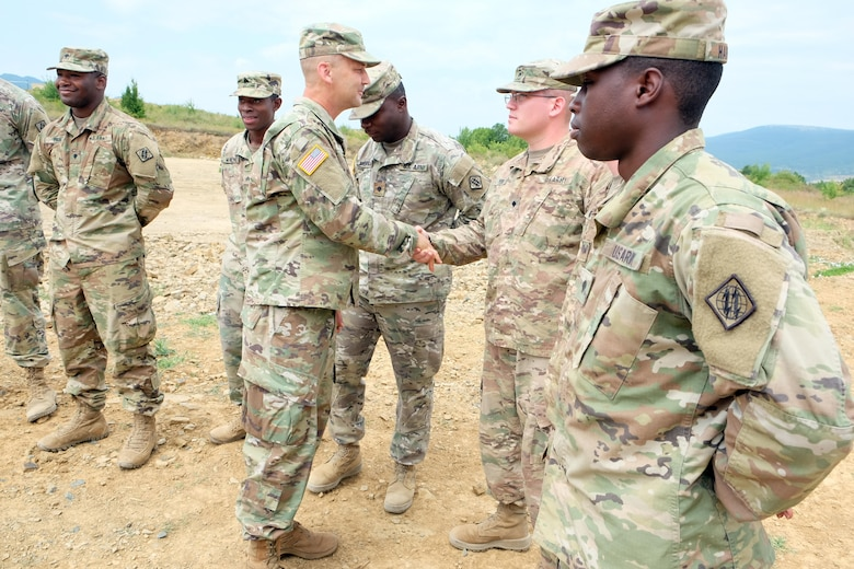Command Sgt. Maj. Raymond Brown, senior enlisted leader of the 7th Mission Support Command, presents coins, July 13, 2017 to the Soldiers of 2nd Platoon, Charlie Co., 44th Expeditionary Signal Battalion, from Grafenwoehr, Germany, for their efforts in keeping communications going for the 21st Theater Sustainment Command's Forward Command Post during Exercise Saber Guardian 17 at Novo Selo Training Area in Bulgaria.
