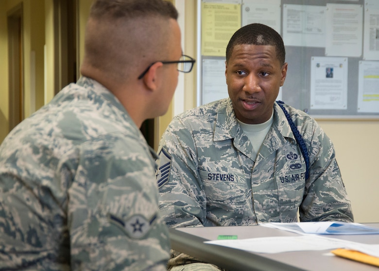 Master Sgt. Michael J. Stevens, United States Air Force School of Aerospace Medicine Military Training Flight chief, briefs a new arrival, Airman Andre Cade, checking into USAFSAM July 6, 2017, at Wright-Patterson Air Force Base, Ohio. Stevens, was named one of the Air Force's 12 Outstanding Airmen of the Year. (U.S. Air Force photo by R.J. Oriez)
