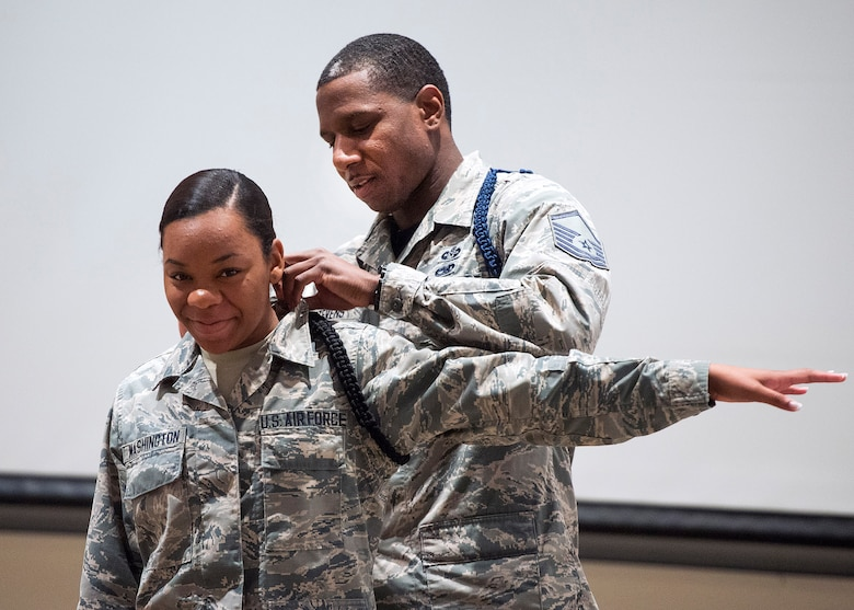 Master Sgt. Michael J. Stevens, United States Air Force School of Aerospace Medicine Military Training Flight chief, pins on Airman Chiara Washington the black rope signifying her as a member of the school's drill team July 7, 2017 on Wright-Patterson Air Force Base, Ohio. Stevens, was named as one of the Air Force's 12 Outstanding Airmen of the Year. (U.S. Air Force photo by R.J. Oriez)