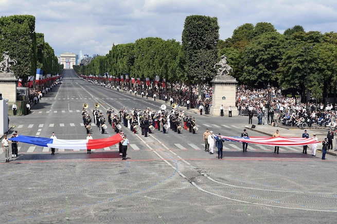 U.S. and French service members display their nations' respective flags during the Bastille Day military parade in Paris, July 14, 2017. Navy photo by Chief Petty Officer Michael McNabb