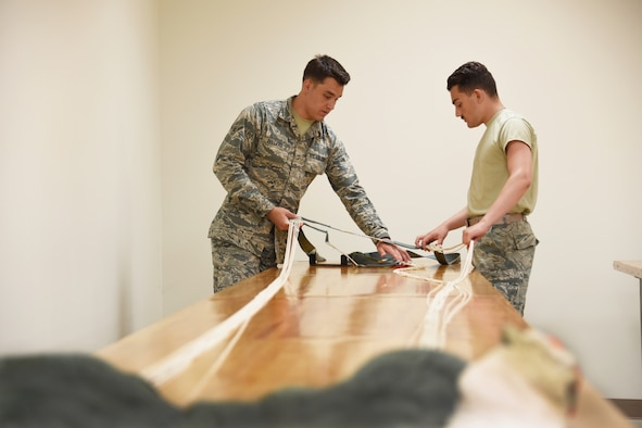 Airmen Bryant Zellers and Anton Trenga, 361st Training Squadron aircrew flight equipment apprentice students ensure that all flight and safety equipment is in perfect working order at Sheppard Air Force Base, Texas. In this course students learn to recover, assemble, inspect and pack the ACES II Recovery parachute. This parachute system is stowed behind the crewman's seat headrest and is projected after the ejection seat is projected from the F-16 aircraft. (U.S. Air Force photo/Liz H. Colunga)