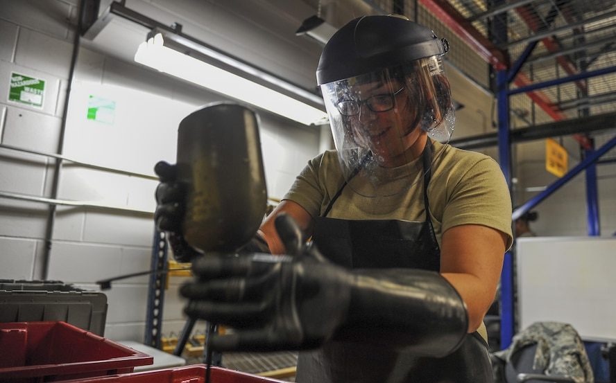 Senior Airman Jordan Parker, a materiel management journeyman with the 1st Special Operations Logistics Readiness Squadron, pours a cleaning solution into a gas mask drinking tube at Hurlburt Field, Fla., July 10, 2017. The chlorine solution is used to clean and sanitize gas masks before being reissued to deploying Air Commandos. (U.S. Air Force photo by Airman 1st Class Isaac O. Guest IV)