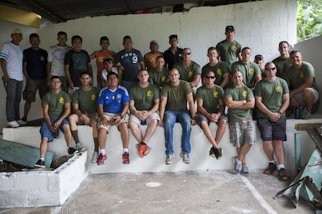U.S. Marines and sailors with the Logistics Combat Element, Special Purpose Marine Air-Ground Task Force - Southern Command, pose for a photo with individuals from the Official School for Rural Community Housing in Guazacapán, Guatemala, July 2, 2017. The Marines and sailors volunteered at the school to make a positive impact in the communities where they work and develop new relationships with the local population. The Marines and sailors of SPMAGTF-SC are deployed to Central America to conduct security cooperation training and engineering projects with their counterparts in Honduras, Guatemala, Belize and El Salvador. (U.S. Marine Corps photo by Cpl. Melissa Martens)