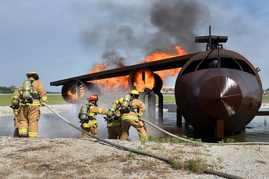 Firefighters from both Offutt Air Force Base and 139th Airlift Wing Fire and Emergency Services from St. Joseph, Missouri participate in a training exercise of a simulated aircraft fire on Offutt AFB, Nebraska, June 6. These types of exercises allows the firefighters to sharpen and enhance their skills they may use on a daily basis. (U.S. Air Force photo by Charles Haymond)