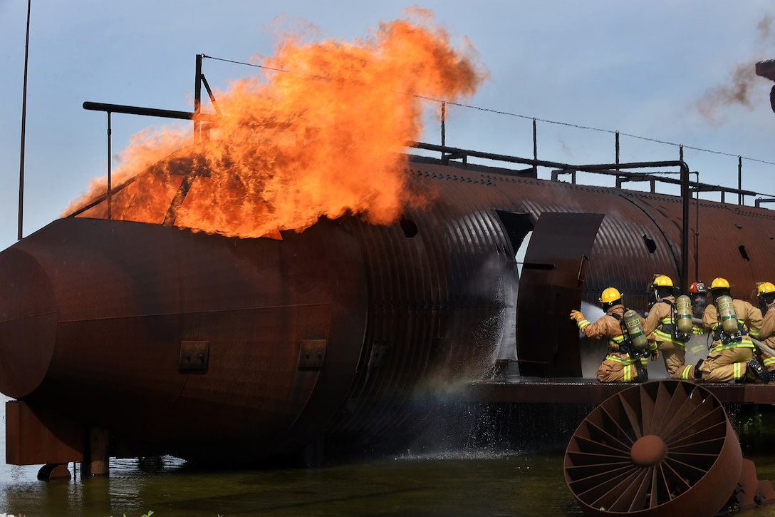 Firefighters from both Offutt Air Force Base, Nebraska and 139th Airlift Wing Fire and Emergency Services from St. Joseph, Missouri participate in a training exercise of a simulated aircraft fire on Offutt AFB, Nebraska, June 6. The exercise provided first-hand experience what tools and techniques are needed to perform the duties of a firefighter on various Air Force bases. (U.S. Air Force photo by Charles Haymond)