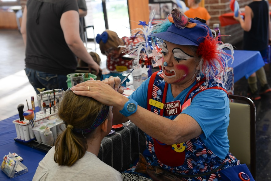Donna Trout, also known as Rainbow Trout the clown, paints children's faces at Offutt's base lake on July 8, 2017 during the annual fireworks display. Several family activities took place at the celebration including face painting, treasure hunt and a performance from the Heartland of America Band. (U.S. Air Force photo by Zachary Hada)