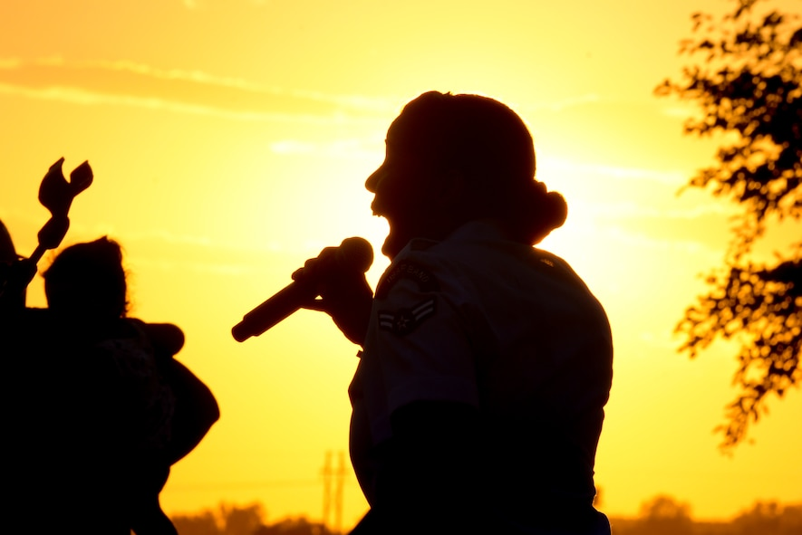 Airman 1st Class Sierra Bailey, a vocalist with the U.S. Heartland of America Band, sings at Offutt's base lake on July 8, 2017 during the annual fireworks display. The Heartland of America Band is a group of Air Force professional musicians whose backgrounds include advanced degrees in music performance and whose broad mastery of musical styles range from classic to contemporary, jazz to country and pop to rock. (U.S. Air Force photo by Zachary Hada)