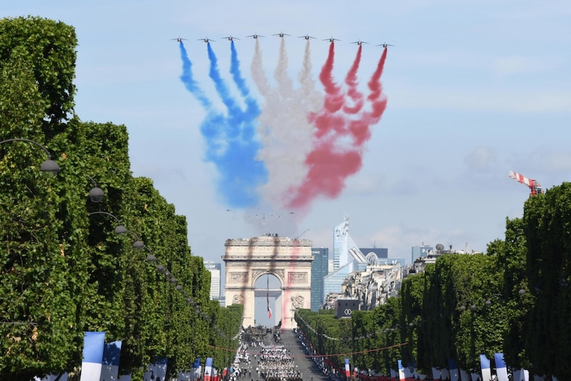French Alphajets, followed by the U.S. Air Force Thunderbirds and two F-22 Raptors, conduct a flyover while displaying blue, white and red contrails during the Military Parade on Bastille Day in Paris, July 14, 2017. Navy photo by Chief Michael McNabb