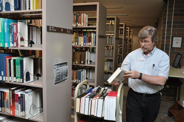 Dwight Goforth, a library technician at the D'Azzo Research Library, places books back into circulation. Today, the library includes more than one million items. (U.S. Air Force photo/Bryan Ripple)