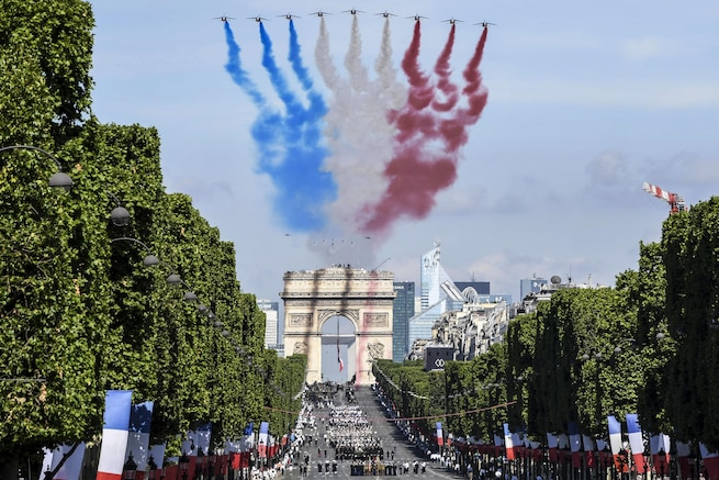 U.S. service members march in the Bastille Day parade in Paris, July 14, 2017, as smoke trails billow overhead from a flyover conducted by French Alpha jets. U.S. troops led the parade in a historic first, to commemorate the centennial of America's entry into World War I and its long-standing partnership with France. Navy photo by Chief Petty Officer Michael McNabb