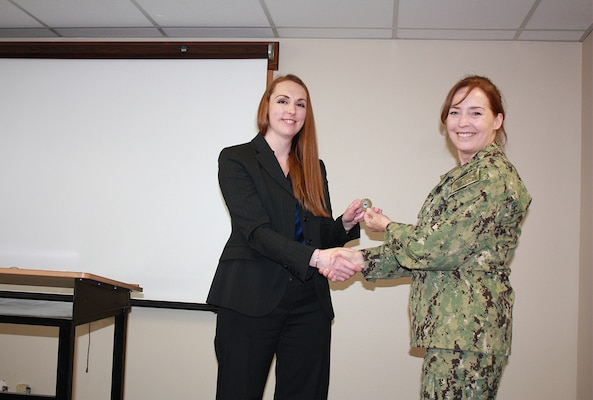 Defense Logistics Agency Land and Maritime Commander Navy Rear Adm. Michelle Skubic presents her commander's coin for excellence to Ryen Joyce during a July 10 site visit and review at DLA Maritime at Puget Sound Naval Shipyard in Bremerton, Wash. Joyce is a material support division manager at DLA Maritime at Puget Sound.