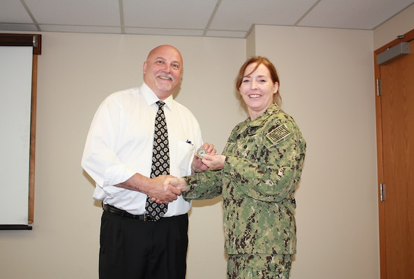 Defense Logistics Agency Land and Maritime Commander Navy Rear Adm. Michelle Skubic presents her commander's coin for excellence to Brian Mueller during a July 10 site visit and review at DLA Maritime at Puget Sound Naval Shipyard in Bremerton, Wash. Mueller serves as deputy director of DLA Maritime at Puget Sound.