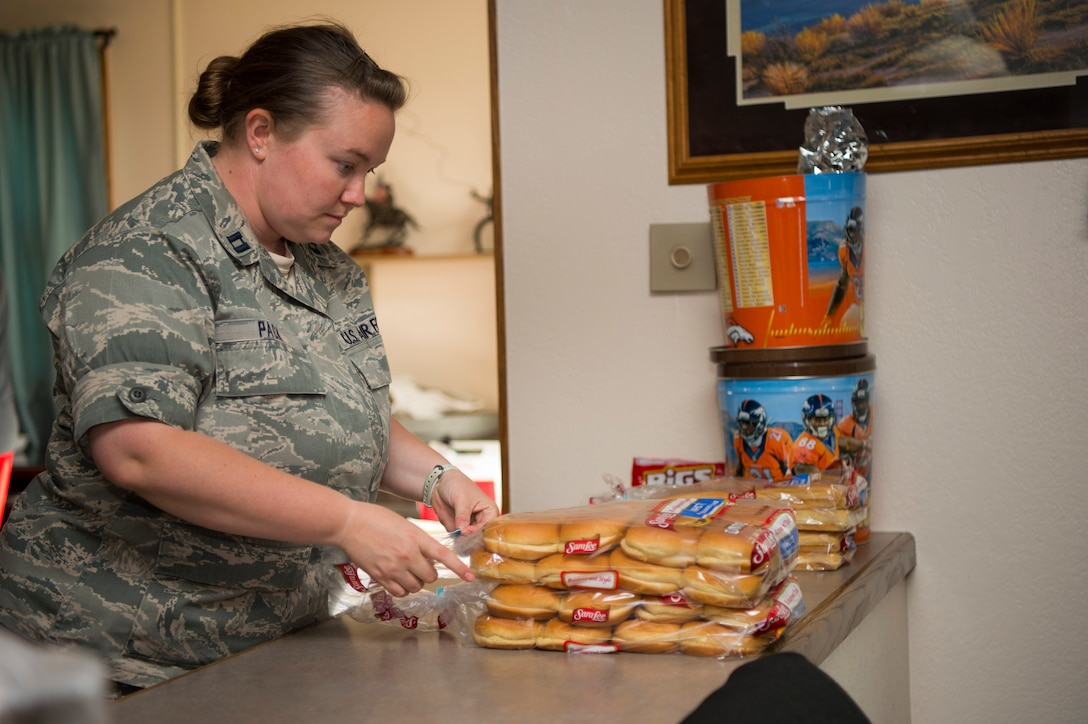 Captain Morgan Pack, 319th Missile Squadron flight commander, prepares plates and buns during the 319th MS code change burger burn in the 90th Missile Wing missile complex, July 12, 2017. Leadership from the 319th MS, along with the assistance of 90th MW chaplains, traversed the missile complex during the squadron's week-long code change, providing food and talking to the Airmen tackling their critical mission. (U.S. Air Force photo by Staff Sgt. Christopher Ruano)