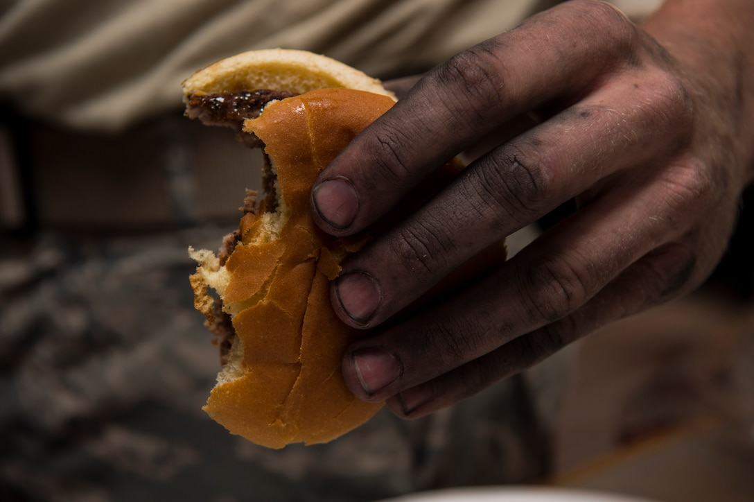 The machine-stained hand of Senior Airman Gabriel Chrum, 90th Missile Maintenance Squadron electro mechanical team technician, grasps a hamburger during the 319th Missile Squadron code change burger burn in the 90th Missile Wing missile complex, July 12, 2017. The different units responsible for cleaning sensitive components in the missile complex were offered a freshly-cooked meal by leaders in the 319th Missile Squadron and 90th MW chaplains. (U.S. Air Force photo by Staff Sgt. Christopher Ruano)