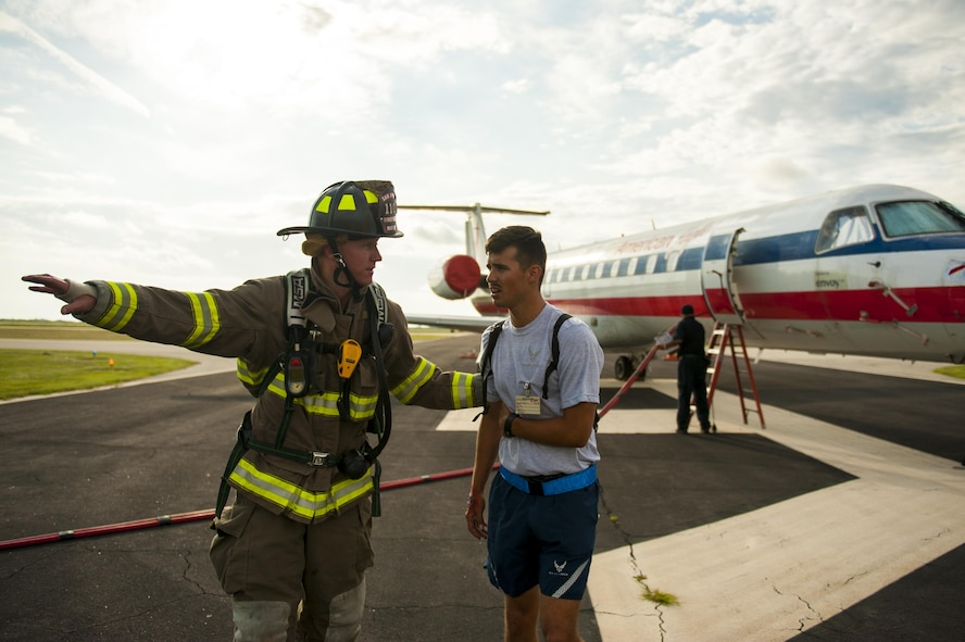 Shane Mathews, San Angelo firefighter, helps a crisis actor get to a safe location during a plane crash exercise at the Mathis Regional Airport San Angelo, Texas, July 13, 2017. Firefighters and other emergency services responded to a simulated plane crash in which a military aircraft collided with a commercial passenger aircraft. (U.S. Air Force photo by Senior Airman Scott Jackson/Released)