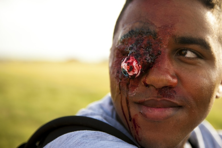 Wearing make-up to simulate an injury, U.S. Air Force Airman 1st Class Knyn Jones, 312th Training Squadron student, awaits medical treatment during a plane crash exercise at the Mathis Regional Airport San Angelo, Texas, July 13, 2017. Jones volunteered as a crisis actor. (U.S. Air Force photo by Senior Airman Scott Jackson/Released)