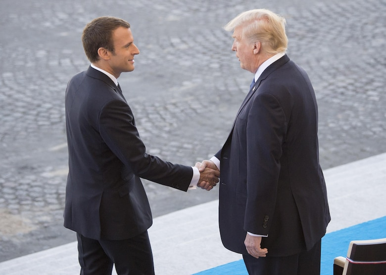 French President Emmanuel Macron welcomes President Donald J. Trump to the reviewing stand for the Bastille Day military parade in Paris, July 14, 2017. Macron and Trump recognized the continuing strength of the U.S.-France alliance from World War I to today.