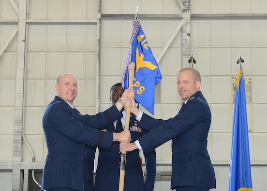 Brig. Gen. Carl Schaefer, 412th Test Wing commander (left), and new U.S. Air Force Test Pilot School commandant, Col. Matthew Higer, pose with the school's guidon during a change of command ceremony in Hangar 1207 July 14. (U.S. Air Force photo by Kenji Thuloweit)