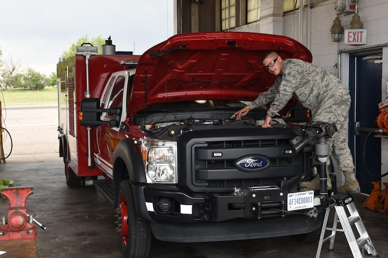 Airman 1st Class Alex Johnson, 90th Logistics Readiness Squadron mission generation and vehicle equipment maintenance apprentice, checks fluid levels in a fire emergency response vehicle, at F.E. Warren Air Force Base, Wyo., July 6, 2017. Maintaining proper fluid level is very important for the upkeep and maintenance of vehicles. (U.S. Air Force photo by Terry Higgins)