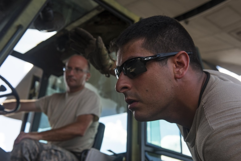 Senior Airman Adam Chudnofsky, right, a loadmaster with the 15th Special Operations Squadron, instructs a forklift driver with the 1st Special Operations Logistics Readiness Squadron to lower the forks while loading an MC-130H Combat Talon II at Hurlburt Field, Fla., July 7, 2017. Aircrew loaded an individual storage unit in preparation for Total Force Exercise 17-3 at Smyrna, Tn. This TFX is a joint forces training exercise that gives members of the 1st Special Operations Wing the opportunity to work in a joint capacity. (U.S. Air Force photo by Tech. Sgt. Jeffrey Curtin)