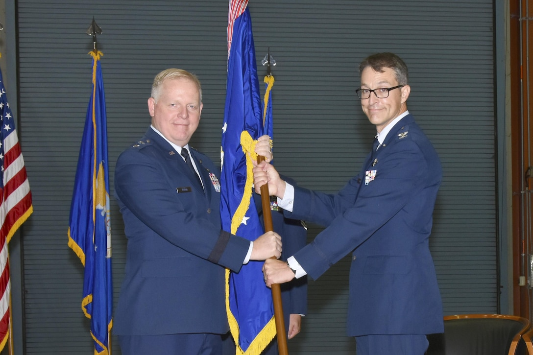 Air Force Test Center Commander Maj. Gen. David A. Harris, left, presents the Arnold Engineering Development Complex flag to the newly-designated commander, Col. Scott A. Cain, during a change of command ceremony July 14 inside the AEDC Large Rocket Motor Test Facility, J-6, located at Arnold Air Force Base, Tennessee. (U.S. Air Force photo/Rick Goodfriend)