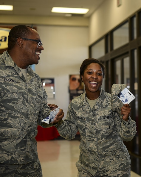 U.S. Air Force Master Sgt. John Brooks III, 355th Comptroller Squadron first sergeant, gives a gift card to Airman 1st Class Alia Washington, 42d Electronic Combat Squadron administration specialist, at Davis-Monthan Air Force Base, Ariz., July 13, 2017. Brooks participated in the quarterly random acts of kindness event that gives back to D-M Airmen and their families. (U.S. Air Force photo by Airman 1st Class Michael X. Beyer)