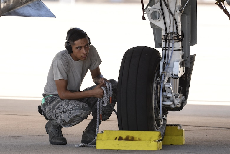 U.S. Air Force Senior Airman Julio España, 355th Aircraft Maintenance Squadron A-10C Thunderbolt II crew chief, waits to release pull chocks for an A-10 at Davis-Monthan Air Force Base, Ariz., July 14, 2017. The first production model of the A-10, the A-10A, was delivered to D-M AFB in Oct. 1975 and the A-10C arrived in Sept. 2007. (U.S. Air Force photo by Senior Airman Mya M. Crosby)