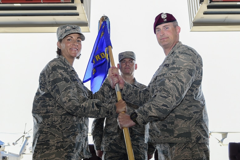 U.S. Air Force Col. Jennifer Short, 23d Wing commander, Moody Air Force Base, Ga., passes the guidon to Col. Jason Pifer, newly appointed 563rd Rescue Group commander, during a change of command ceremony at Davis-Monthan Air Force Base, Ariz., July 14, 2017. Pifer is a combat rescue officer and prior commander of the 48th Rescue Squadron at Davis-Monthan AFB. (U.S. Air Force photo by Staff Sgt. Chris Drzazgowski)