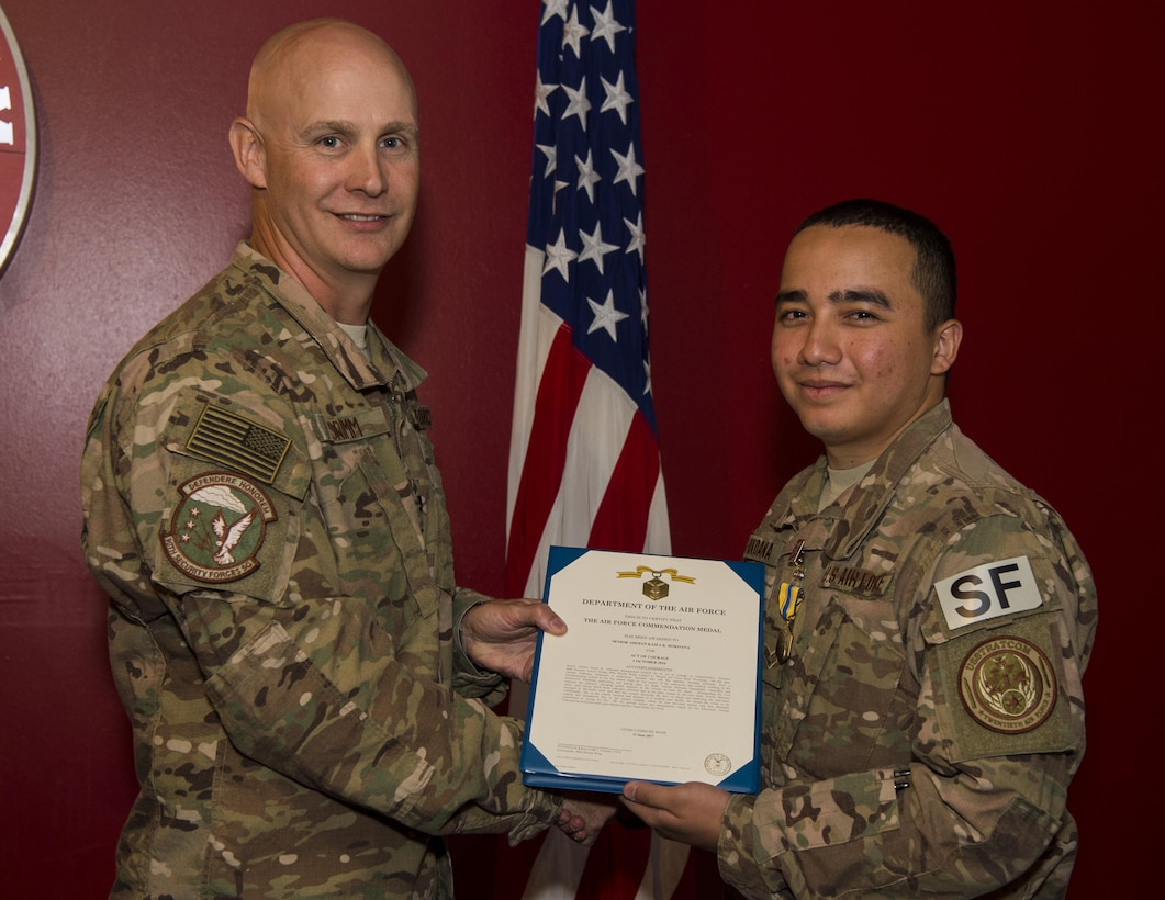 Col. John Grimm, 90th Security Forces Group commander, presents Senior Airman Kaiea Hokoana, 90th Security Forces Squadron installation patrolman, with the Air Force Commendation Medal in Cheyenne, Wyo., July 14, 2017. Hokoana received this medal for his role in providing first responder assistance which contributed to saving a motorist's life on Oct. 1, 2016 while on leave in Maui, Hawaii. (U.S. Air Force photo by Staff Sgt. Christopher Ruano)