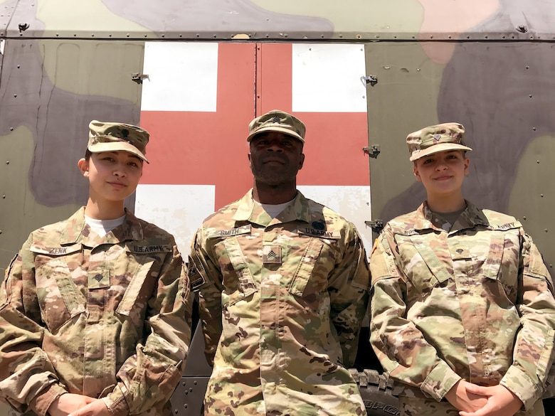Spc. Leia Zenk, left, Sgt. Rashaun Smith, center, and Spc. Lisa Rose, right, Army Reserve Soldiers with the 7th Mission Support Command's Medical Support Unit – Europe, pose in front of the Troop Medical Clinic July 14, 2017 at Novo Selo Training Area in Bulgaria. The three Soldiers stayed busy during Exercise Saber Guardian 17, learning new jobs and volunteering their skills at the clinic.