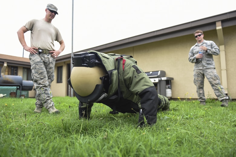 U.S. Air Force Academy Cadet 2nd Class Harry McMahon performs a push up in an explosive ordnance disposal suit at Kunsan Air Base, Republic of Korea, July 11, 2017 while U.S. Air Force E.O.D. members observe him during the cadet's immersion visit. The visit was part of the Air Force Academy's Operation Air Force program. Operation Air Force which takes rising juniors in the Air Force Academy to different bases across the Air Force to shadow and learn about their respective missions. (U.S. Air Force photo by Senior Airman Michael Hunsaker/Released)