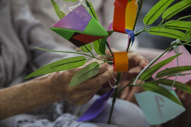 Kikuko Shinjo, a Kinjuen Nursing Home resident, helps tie a wish to a bamboo branch during a nursing home visit with the Marine Corps Air Station Iwakuni Cultural Adaptation Program at Iwakuni City, Japan, July 7, 2017. The nursing home invited tenants of MCAS Iwakuni to celebrate Tanabata, also known as the star festival. Participants in the event wrote their wish on a colorful piece of paper and tied it to a bamboo branch so the wind can carry it, let it manifest and take it to the stars. (U.S. Marine Corps photo by Lance Cpl. Gabriela Garcia-Herrera)