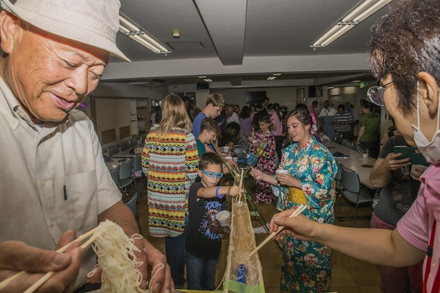 Marine Corps Air Station Iwakuni and Kinjuen Nursing Home residents eat somen nagashi, or sliding somen noodles, during a nursing home visit with the MCAS Iwakuni Cultural Adaptation Program in Iwakuni City, Japan, July 7, 2017. The nursing home invited tenants of the air station to celebrate a Tanabata, also known as the star festival. It gave tenants of the air station a taste of Japanese culture and friendship. (U.S. Marine Corps photo by Lance Cpl. Gabriela Garcia-Herrera)