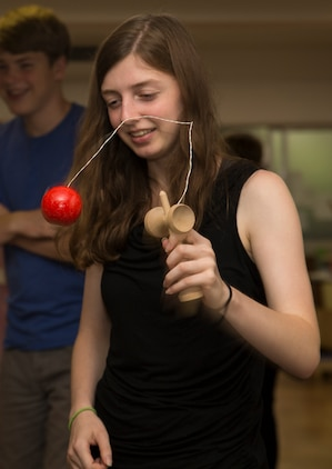 Hannah Walker, a native of Michigan and Marine Corps Air Station Iwakuni visitor, plays with a kendama toy during a visit to Kinjuen Nursing Home in Iwakuni City, Japan, July 7, 2017. The invitation to the nursing home was set up through the MCAS Iwakuni Cultural Adaptation Program to celebrate Tanabata, also known as the star festival. It gave tenants of the air station a taste of Japanese culture and friendship. (U.S. Marine Corps photo by Lance Cpl. Gabriela Garcia-Herrera)