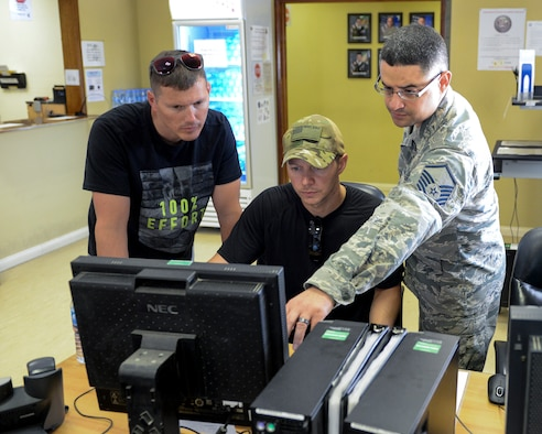 U.S. Air Force Master Sgt. Roberto Pagan, financial services flight chief assigned to the 379th Expeditionary Comptroller Squadron, Financial Services Flight, assists military members at a self-help computer located in the finance building at Al Udeid, Air Base, Qatar, June 13, 2017. The FMF assists deployed military members with travel pay, military pay and dispersal of funds. (U.S. Air National Guard photo by Tech. Sgt. Bradly A. Schneider/Released)