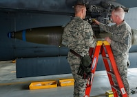 (From right) Chief Master Sgt. Alan Boling, Eighth Air Force command chief, speaks with Tech. Sgt. Cory Erickson, 5th Maintenance Group load standardization crew member, beneath a B-52H Stratofortress wing at Minot Air Force Base, N.D., July 10, 2017. Boling participated in a GBU-31V1 bomb load and was inducted as an honorary B-52 weapons loader. (U.S. Air Force photos/Senior Airman J.T. Armstrong)