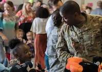 A girl is excited by a toy a U.S. Army captain picked up from one of the tables at the Military Kids Appreciation Day at Dobbins Air Reserve Base, Ga. July 9, 2017. The 94th Airlift Wing partnered with the Kids Wish Network, a national children's charity, to host the event that supported Dobbins military members and their children. (U.S. Air Force photo by Staff Sgt. Andrew Park)