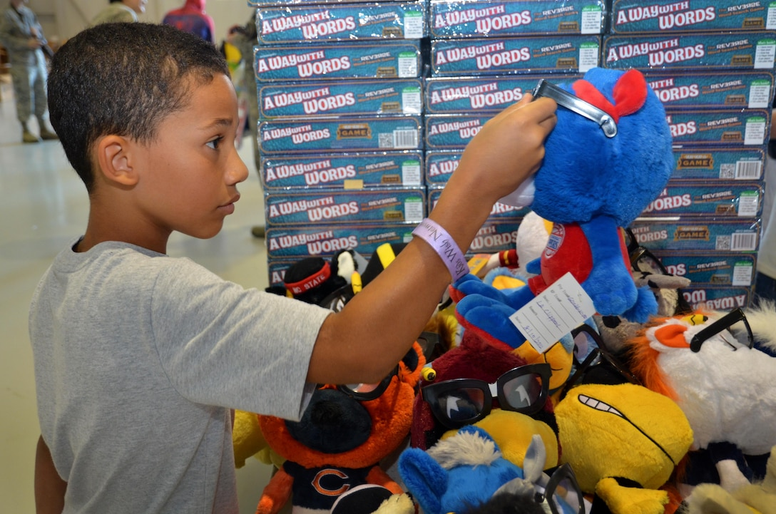 A child looks at a stuffed animal at the Military Kids Appreciation Day at Dobbins Air Reserve Base, Ga. July 9, 2017. Kids Wish Network brought new toys, educational items, games and other necessities for service members' children. (U.S. Air Force photo by Senior Airman Lauren Douglas)