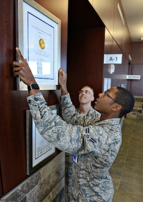 While 72nd Medical Group Commander Col. Christopher Grussendorf watches, Airman 1st Class Jason Pannell, with the 72nd Medical Support Squadron, carefully hangs a certificate from The Joint Commission, bestowing a three-year accreditation to the 72nd MDG by meeting the requirements for the Ambulatory Health Care Accreditation Program.