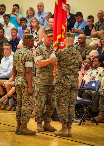 Col. Peter D. Buck (center) transfers the battle standard to Col. Timothy P. Miller (right) during a change of command ceremony aboard Marine Corps Air Station Beaufort, July 7. During the ceremony, Buck transferred responsibility of commanding officer of MCAS Beaufort to Miller. Miller, recently served at U.S. Pacific Command as the Warfighting Exercises Branch Chief. Buck, who assumed command on Feb. 13, 2014, is retiring from the Marine Corps after 30 years of dedicated service.