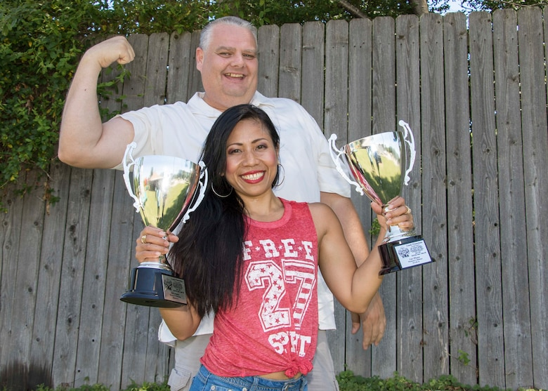 Shane and Edna Boehmer posing with Edna's 2017 National Physique Committee Battle on the Bluff Bodybuilding Contest trophies.