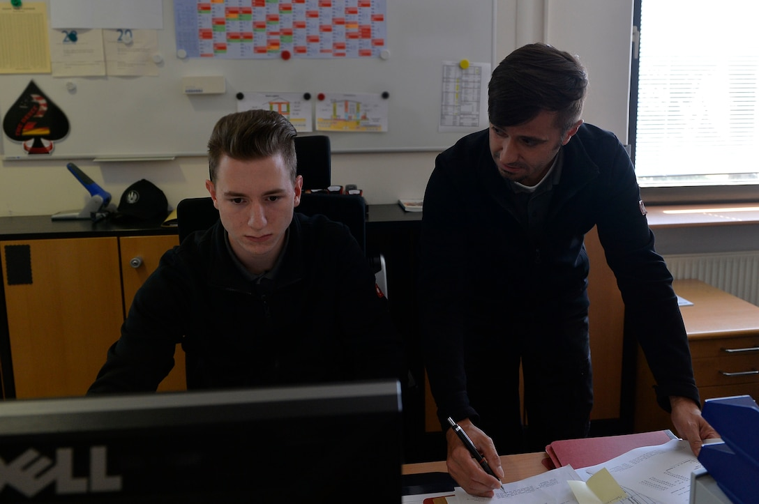 Andreas Lorenz, 435th Construction and Training Squadron supervisory purchasing agent (right), coaches his apprentice, Felix Myer, 435th CTS administrative service clerk, on computer operations on Ramstein Air Base, Germany Jul. 13, 2017. The 435th CTS's three-year apprenticeship program provides vocational training opportunities for local national youth. (U.S. Air Force photo by Airman 1st Class Joshua Magbanua)