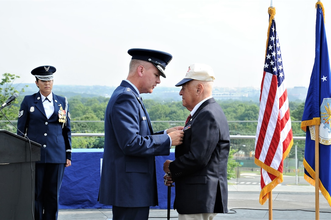 "Maj. Gen. James A. Jacobson (second from right), Air Force District of Washington commander, pins a Purple Heart ribbon on World War II veteran, Lt. John Pedevillano, during an award presentation ceremony July 14, 2017 at the U.S. Air Force Memorial, Arlington, Va. Pedevillano, a B-17 bombardier pilot, and his crew assigned to the 306th Bomb Group of the ""Mighty Eighth"" Air Force were shot down during a bombing mission in airspace over Nazi Germany on April 24, 1944. (Air Force photo by Staff Sgt. Joe Yanik)"