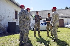 219th RED HORSE Squadron personnel and Slovenian Armed Forces members meet to discuss progress and needs at the Bile barn site Pocek base, near Postonja, Slovenia June 9, 2017. The 219th RHS replaced plumbing, updated electrical wiring, built walls to insulate a water tank and added shelving for the barn which will be used as range control for Exercise Immediate Response.  (U.S. Air National Guard photo/Staff Sgt. Lindsey Soulsby)