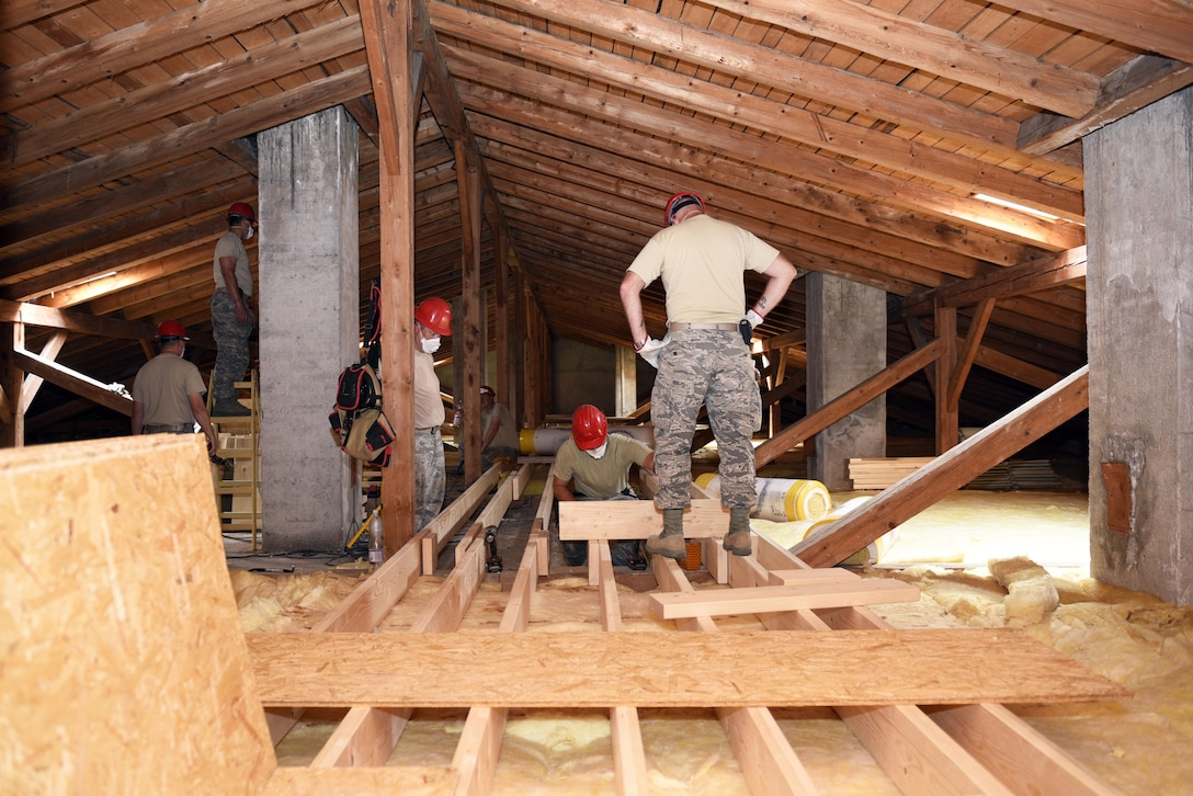 Members of the 219th RED HORSE Squadron verify joists are level on a catwalk in the attic of a barracks June, 14, 2017, Pocek base, near Postonja, Slovenia. The catwalk was built as a way to easily maneuver the attic for future maintenance. (U.S. Air National Guard photo/Staff Sgt. Lindsey Soulsby)