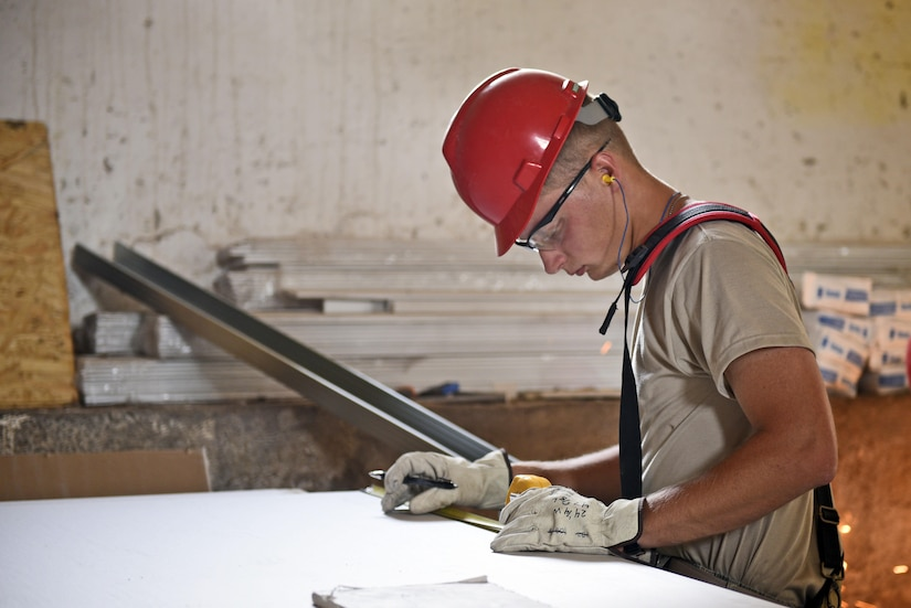 Airman 1st Class Michael Wisherd, 219th RED HORSE Squadron airfields apprentice, measures a piece of sheetrock June 14, 2017 at the Bile barn, Pocek Base, near Postonja, Slovenia. Wisherd is built a wall to insulate a water tank for Exercise Immediate Response to occur later in 2017. (U.S. Air National Guard photo/Staff Sgt. Lindsey Soulsby)