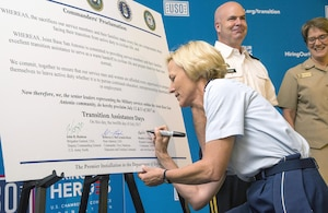 Brig. Gen. Heather Pringle (left), commander of the 502nd Air Base Wing and Joint Base San Antonio, signs the Commanders' Proclamation July 12 during the Transition Assistance Days at the Fort Sam Houston Community Center as Brig. Gen. John Hashem, deputy commanding general, U.S. Army North; and Rear Adm. Rebecca McCormick-Boyle, commander, Navy Medicine Education and Training Command, look on.