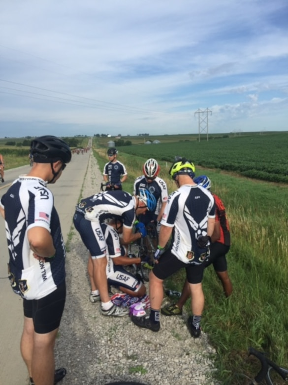 "Members of the Air Force cycling team assist a cycler whos bike tire went flat at RAGBRAI 2016. The team members are known as ""guardian angels"" on the 500-mile bike ride because they stop to help every person they find in distress along the route."